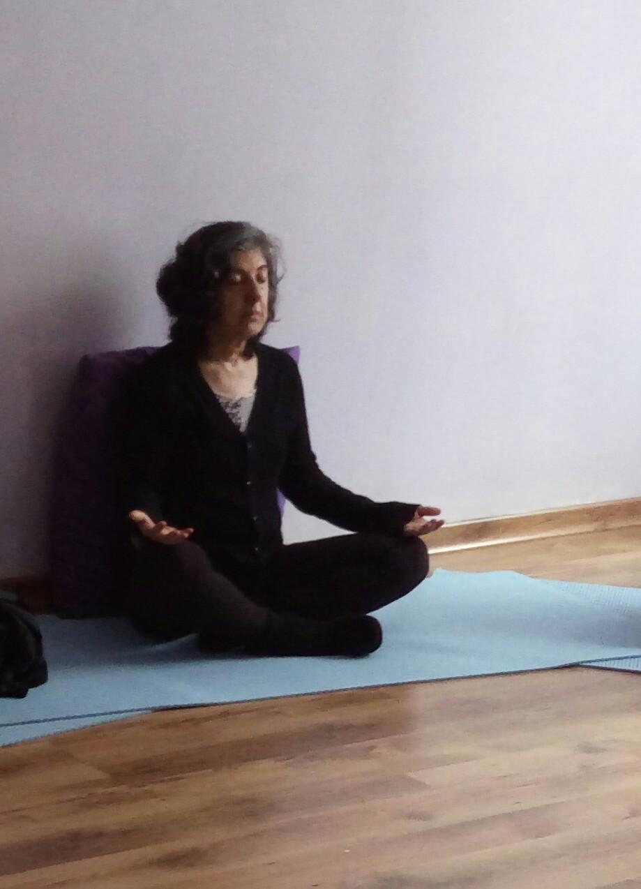 aluna em posição de pernas de índio sentada no tapete azul de Yoga e mãos repousadas sobre os joelhos de palmas para cima e olhos fechados