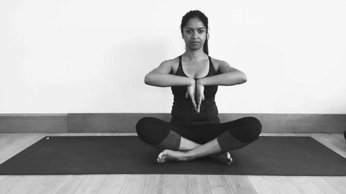 moça de roupa preta sentada em pernas de índio com as mãos unidas no peito com os dedos para baixo, em posição de oração invertida