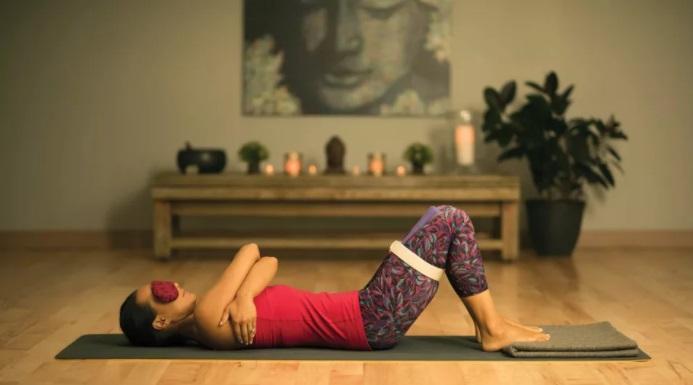 mulher com blusa rosa e calça roxa estampada, protetor de olhos, deitada em tapetinho, faixa branca prendendo as pernas unidas realizando a postura