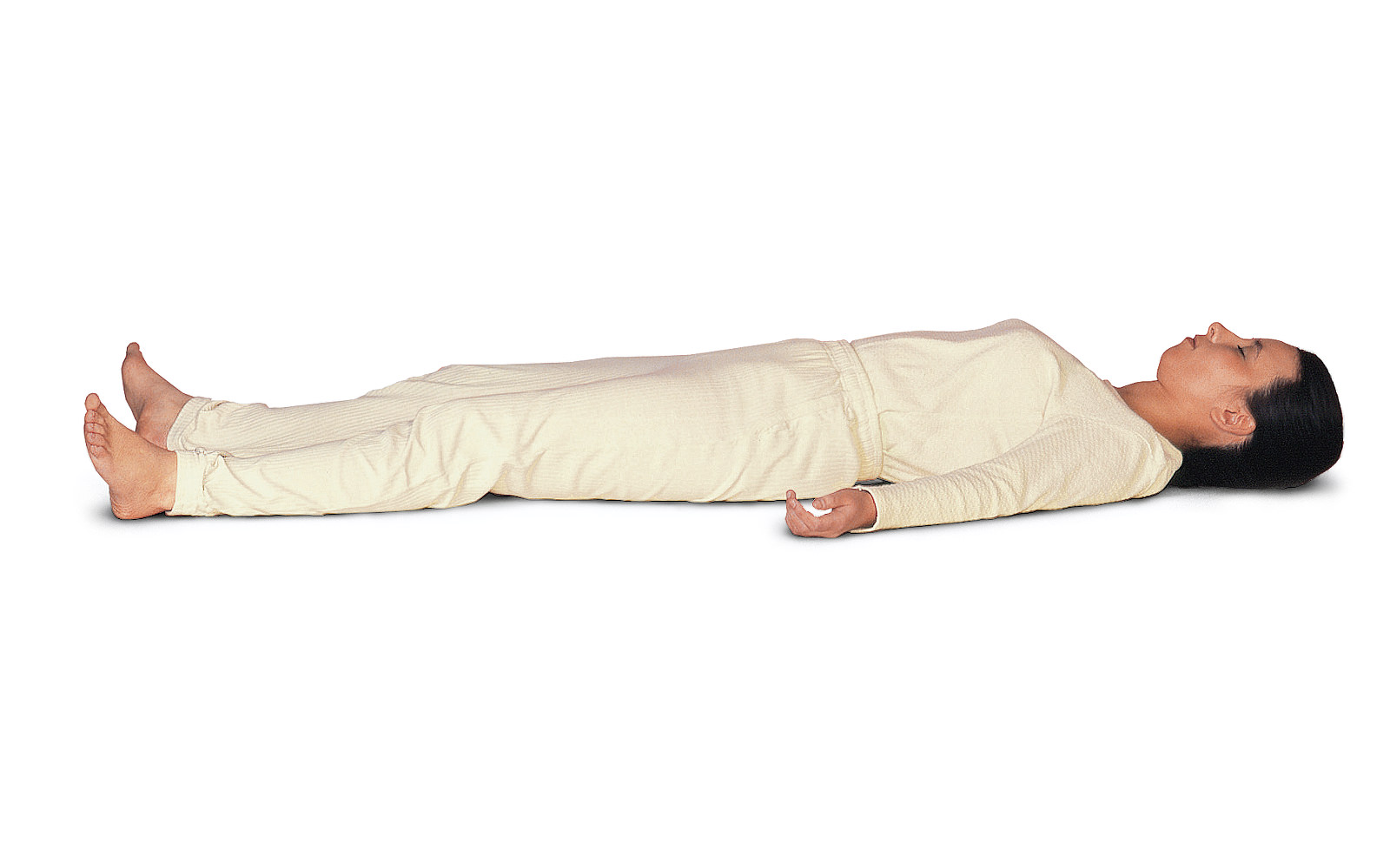 mulher de calça e blusa brancos deitada em fundo infinito branco, de barriga para cima, cabelos escuros e presos, relaxando no solo