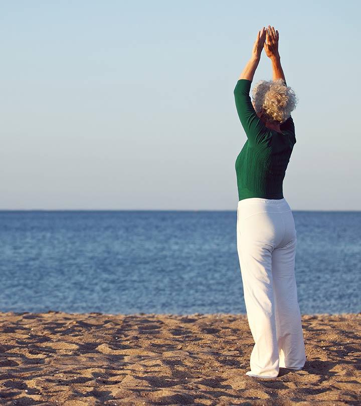 Mulher idosa em areia da praia com mar ao fundo, calça branca e blusa verde, de costas com braços levantando e mão unidas acima da cabeça