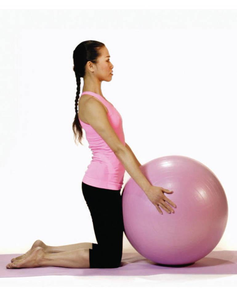 mulher oriental de perfil com trança nos cabelos, veste calça preta e blusa rosa, ajoelhada segura uma bola de Pilates rosa