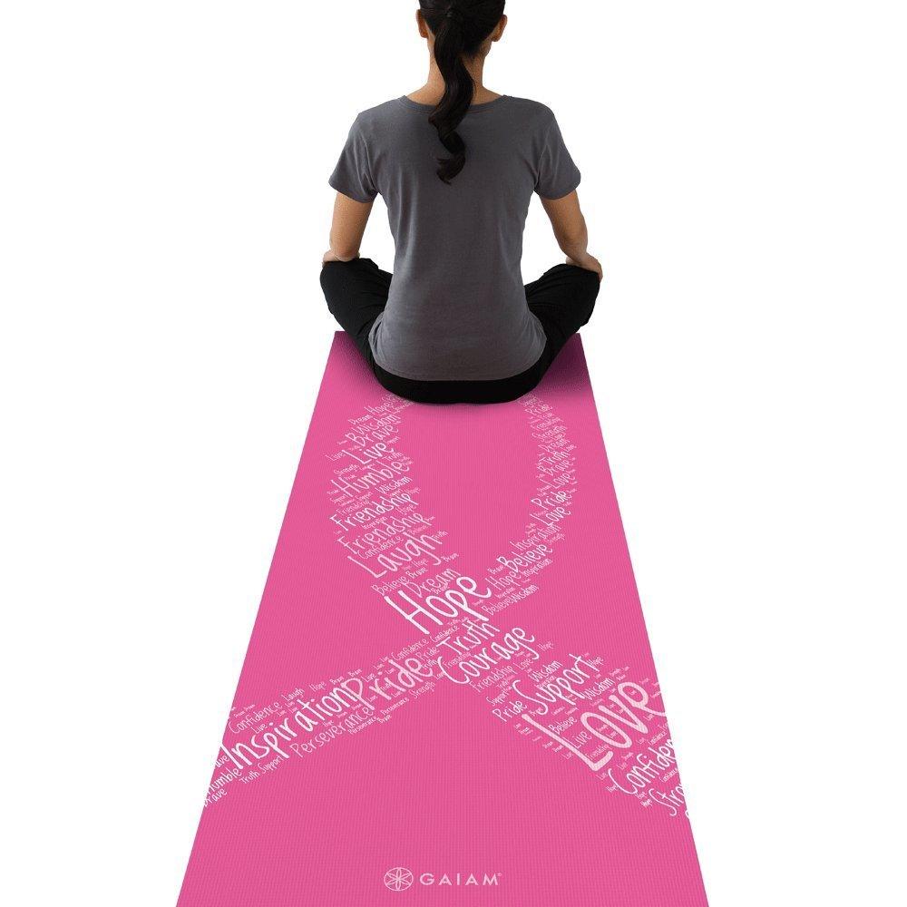 mulher sentada de costas com blusa cinza e calça preta em cima de mat de yoga rosa com o símbolo da fita de causa branco desenhado
